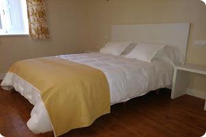 Cama grande de la habitación del hostal comoda