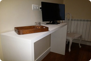 Tele y mesa de la habitación del hostal